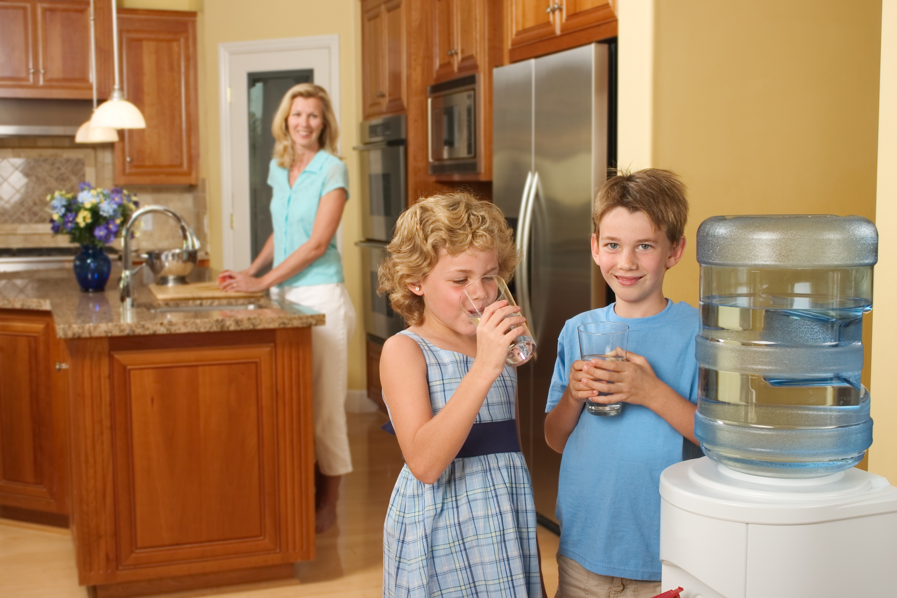 Children at home drinking purified water from a water cooler.