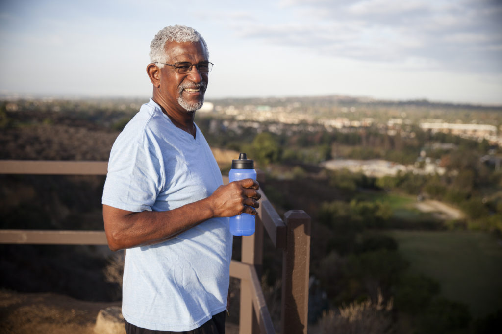 A senior black man takes a drink of water during his outdoor working